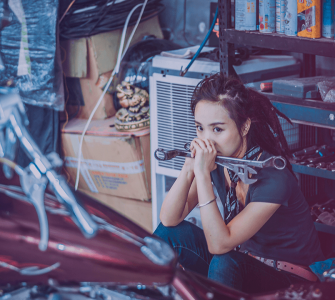 A woman with tools looking pensive