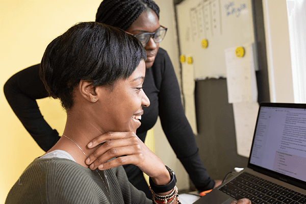 A woman with a mentor looking at a computer
