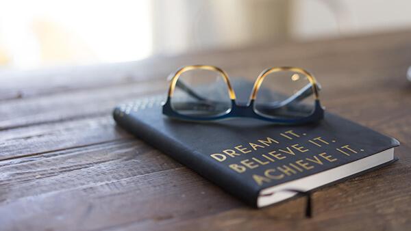 Dream it. Believe it. Achieve it. Book and sunglasses.